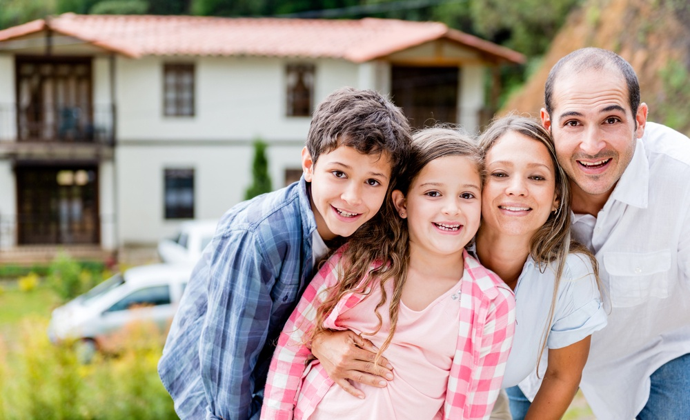 Happy family outside their house in the countryside