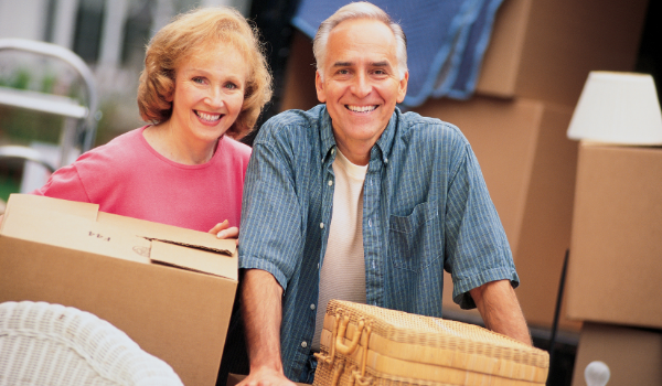older couple carrying moving boxes